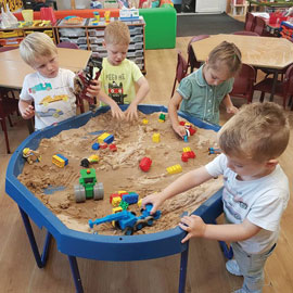 Nursery children playing with sand pit