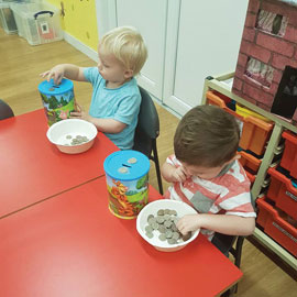 Children playing with moneyboxes in nursery